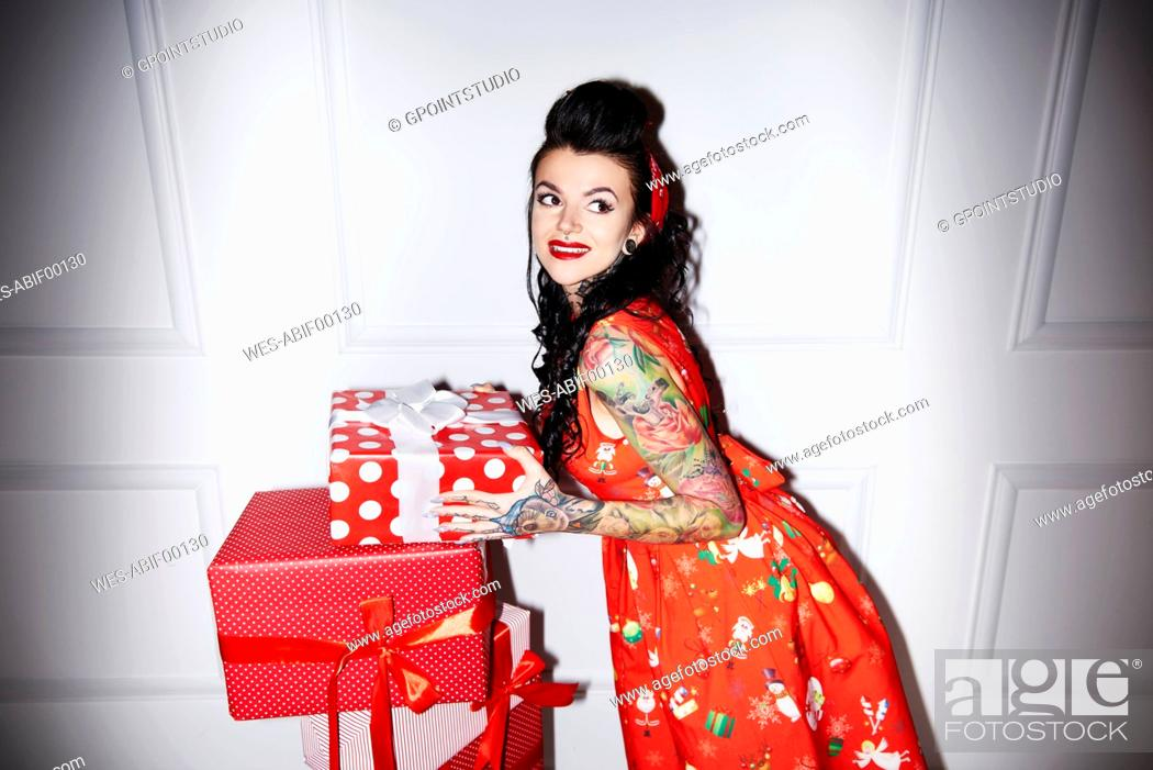 Stock Photo: Portrait of tattooed woman with stack of gifts.
