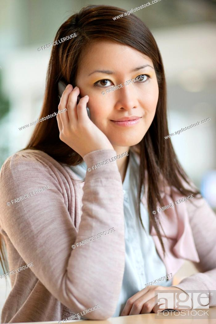 Stock Photo: Portrait of a businesswoman talking on a mobile phone in an office.