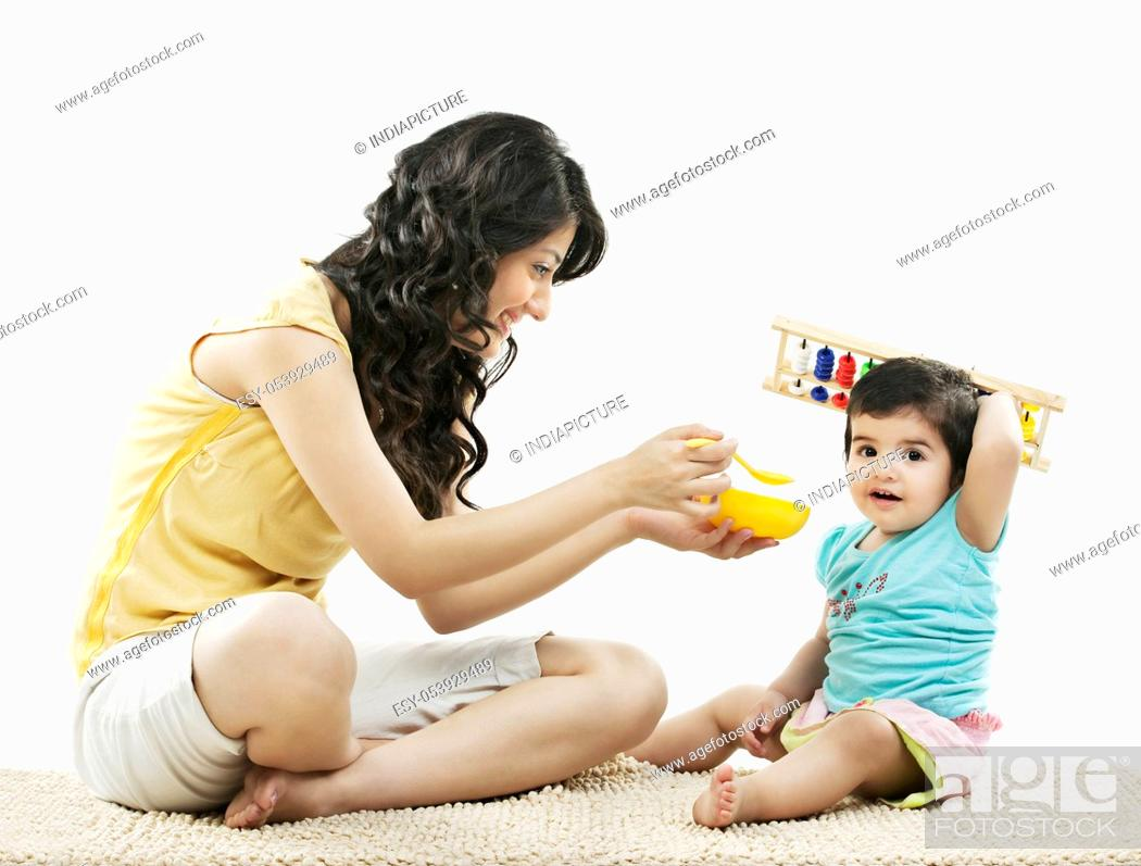 Stock Photo: Mother trying to feed her child.