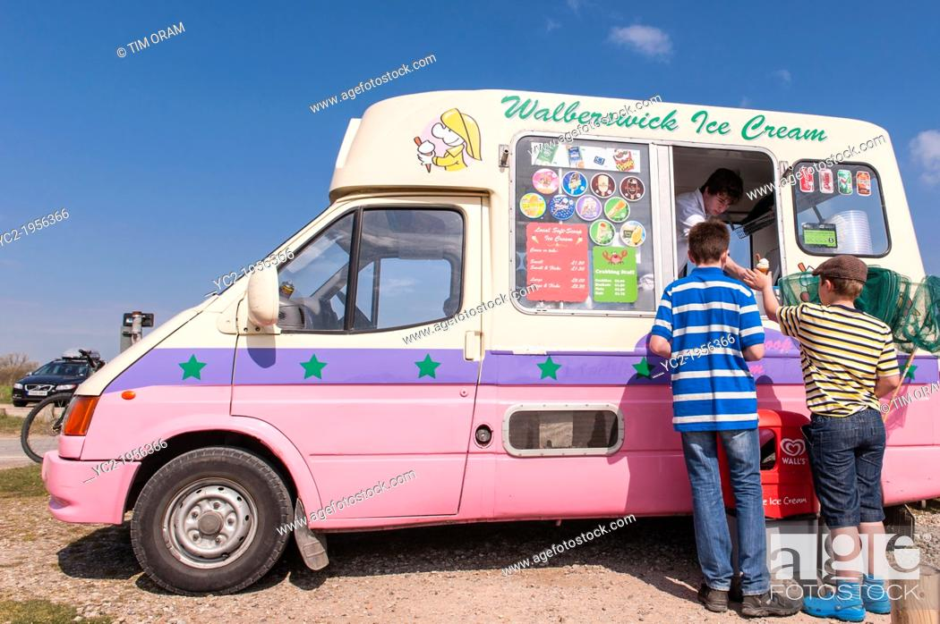 Stock Photo: Walberswick, Suffolk, UK. 6th May 2013. Two boys enjoy the sunny weather on Bank Holiday Monday 6th of May 2013 as they buy ice creams at Walberswick, Suffolk.
