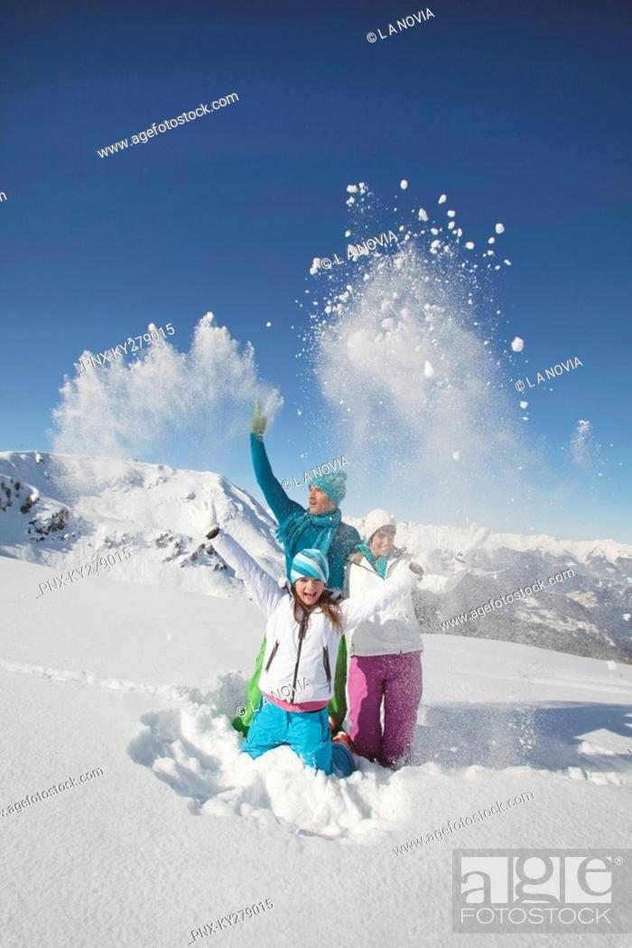 Stock Photo: Couple and daughter in ski wear, throwing snow in air.