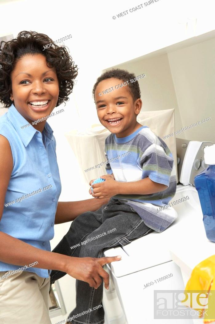 Stock Photo: Mother and son 3-6 in laundry room.