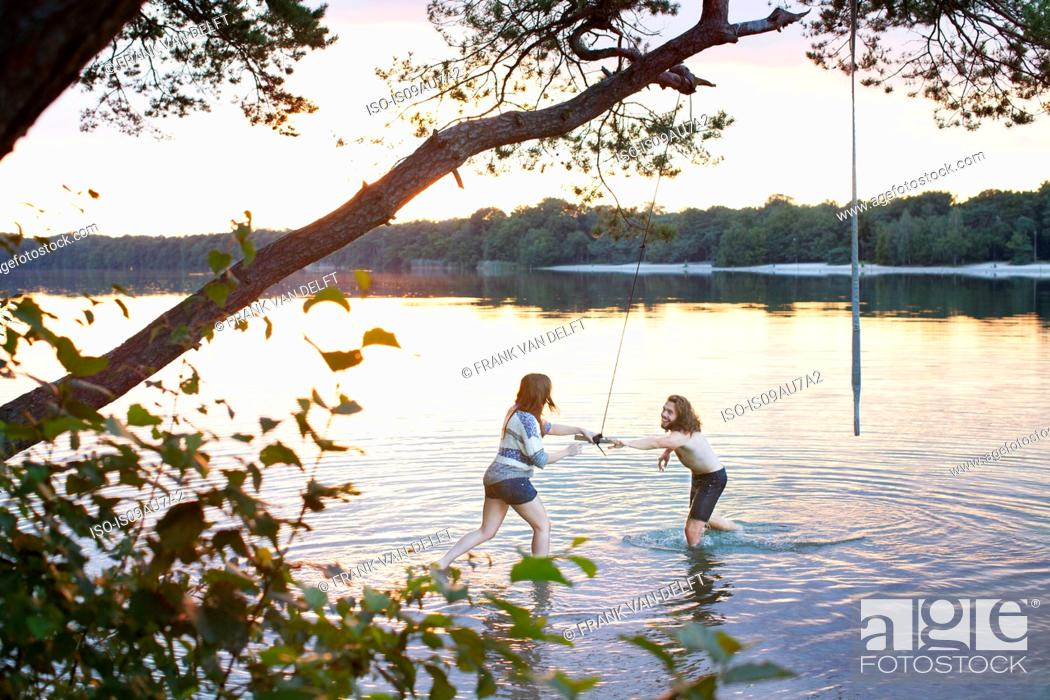 Stock Photo: Young couple playing in lake.