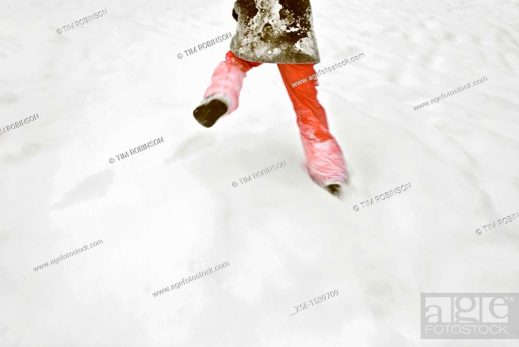 Stock Photo: Rearview legs and lower torso 8 year girl walking in snow.