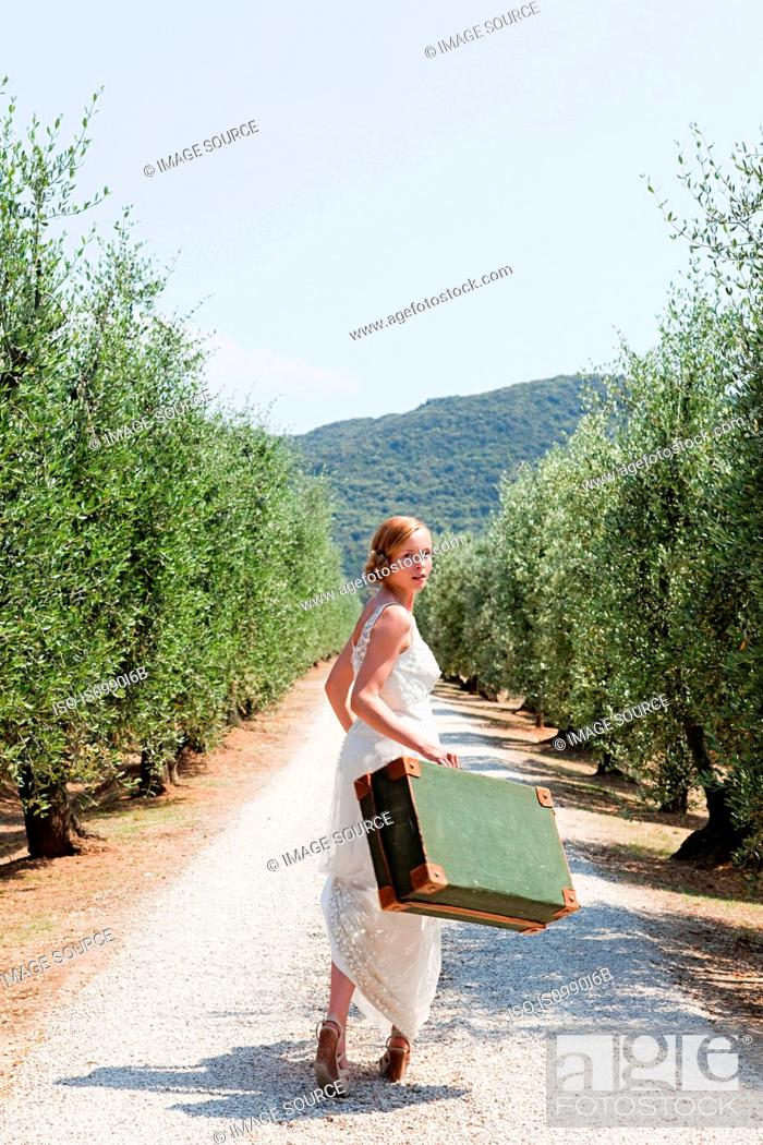 Stock Photo: Bride carrying suitcase on country road.