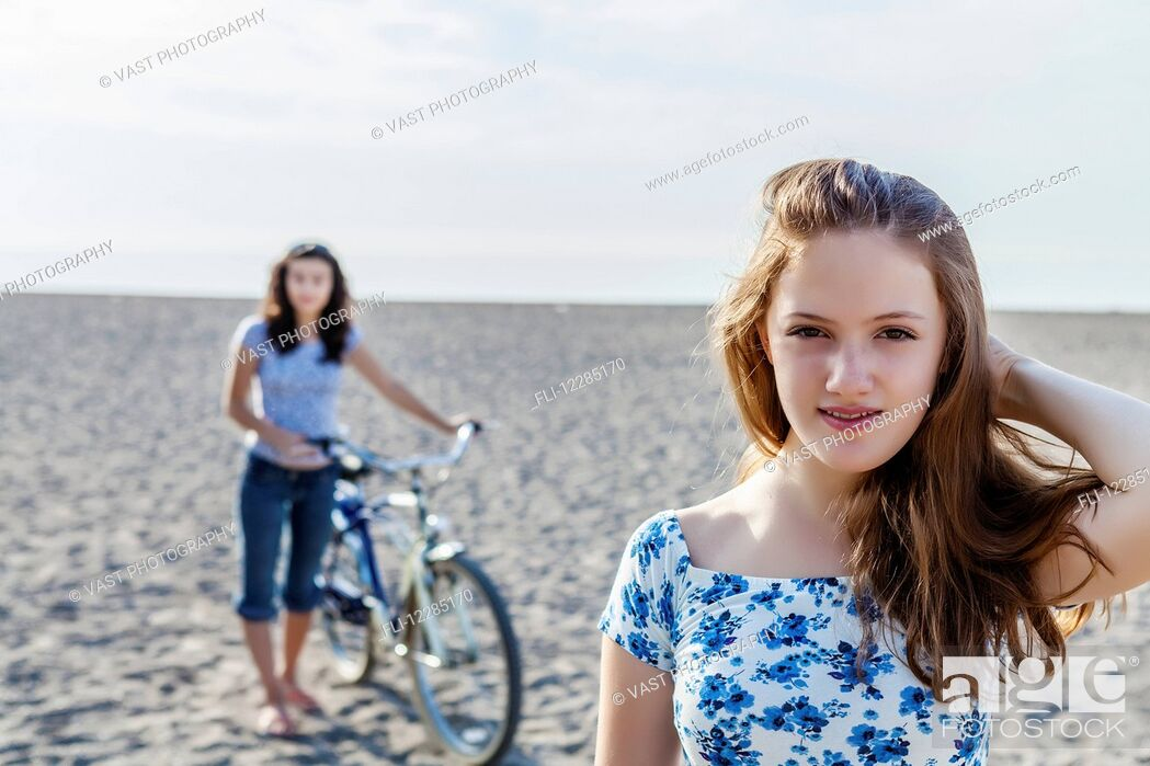 Stock Photo: Two girls standing on a beach with bike; Toronto, Ontario, Canada.