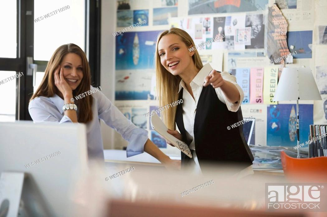 Stock Photo: Two women in office, smiling.