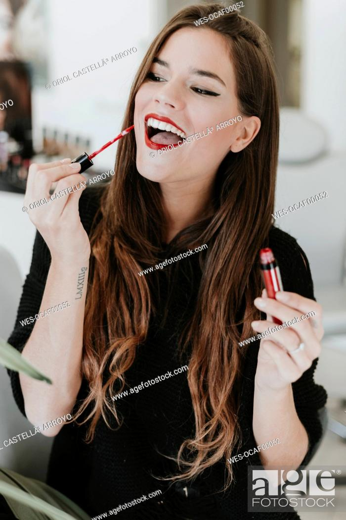 Stock Photo: Portrait of happy young woman applying lipstick.