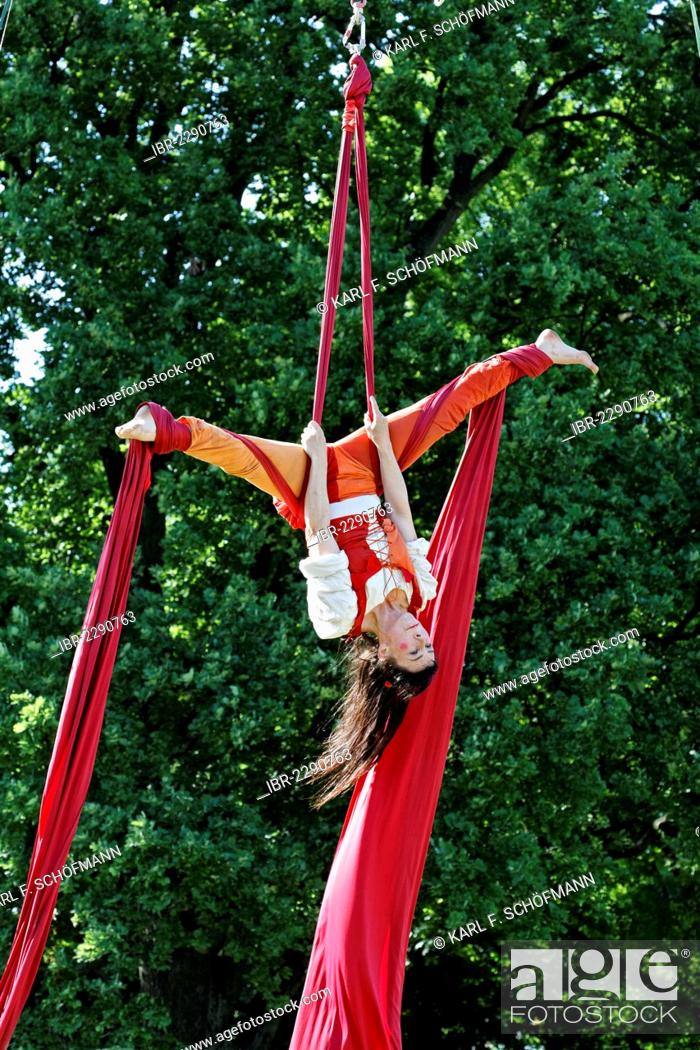 Artist in a medieval costume hanging upside down on a