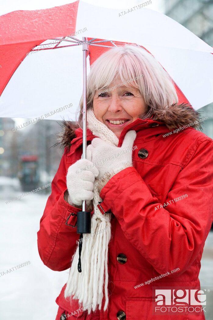 Stock Photo: Freezing elderly person with umbrella.