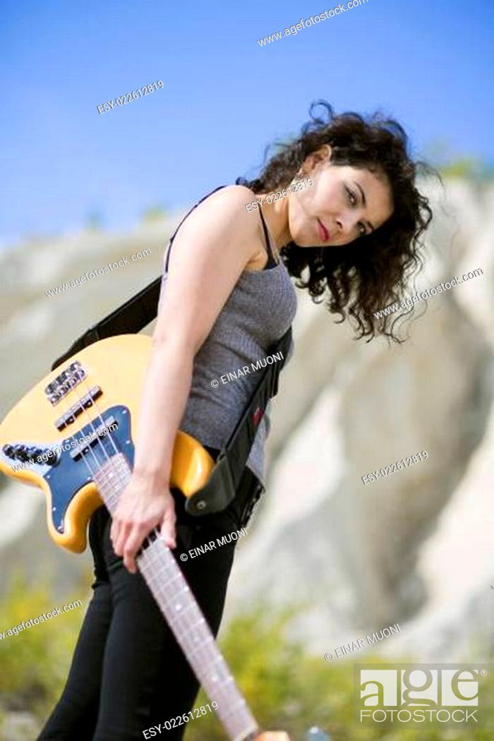 Stock Photo: Nice looking young woman posing with guitar.