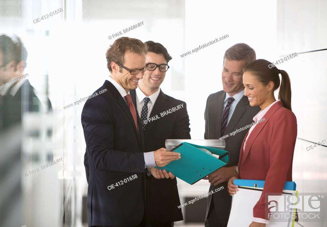 Stock Photo: Business people talking in office hallway.