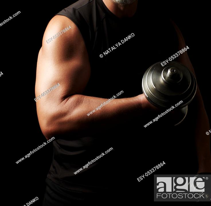 Stock Photo: adult man in black clothes holds steel dumbbells in his hands, his muscles are tense, low key, sports background.