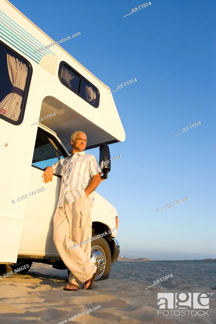 Stock Photo: Mature man by motor home on beach, arm on door, low angle view.