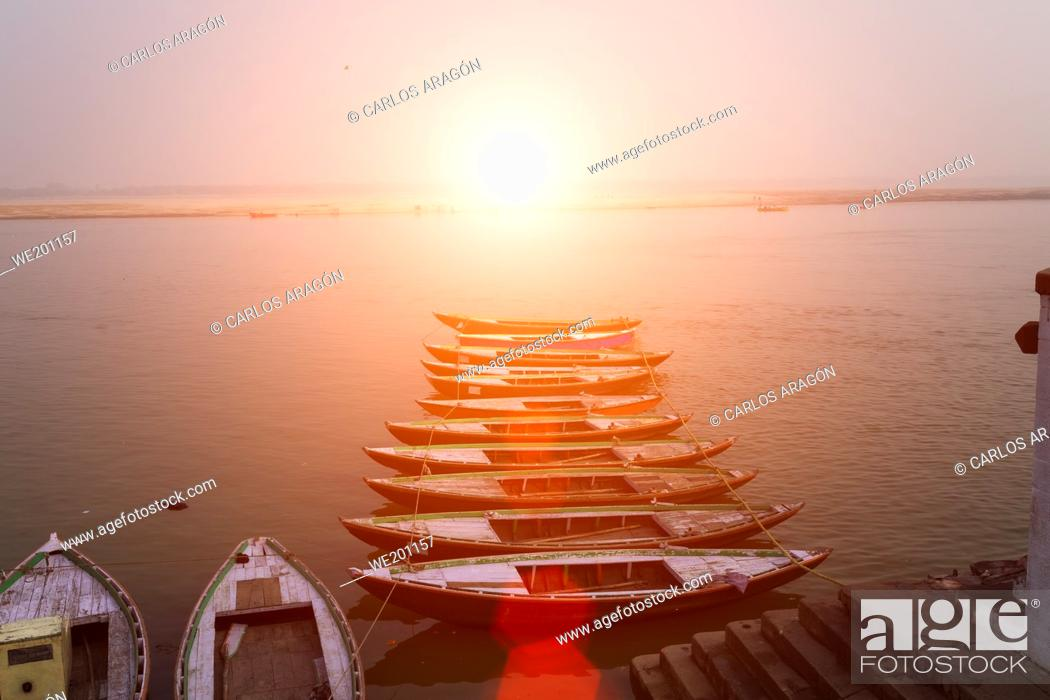 Stock Photo: Sunrise over the Ganges river, with tour boats in the foreground in Varanasi, India.