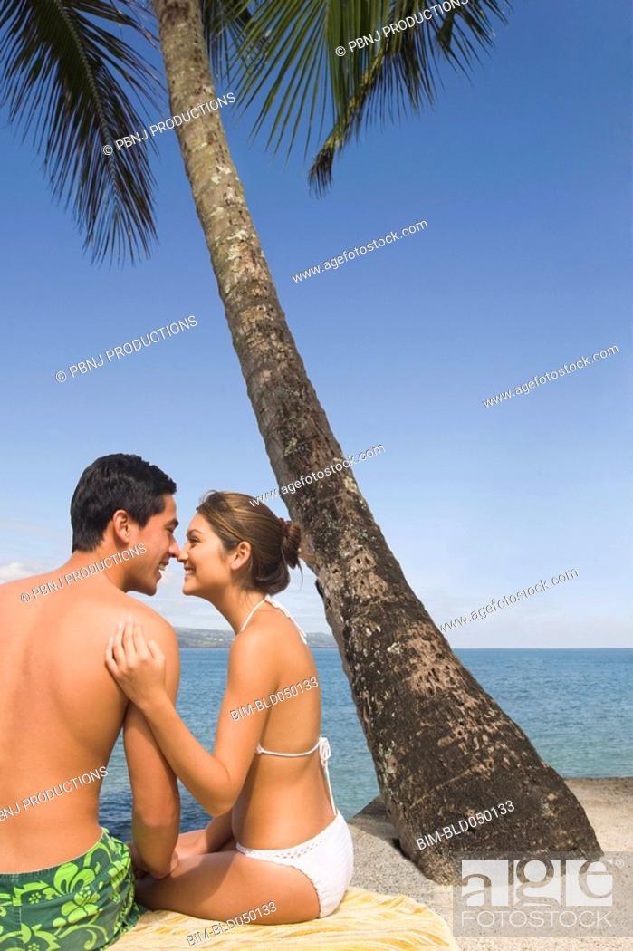 Stock Photo: Asian couple sitting on beach.