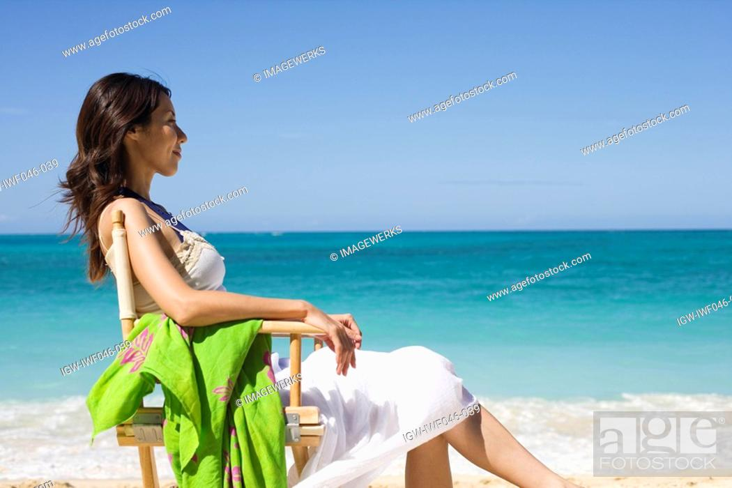 Stock Photo: A young woman sitting on chair at beach.