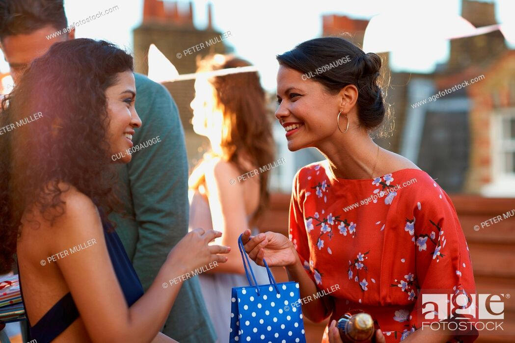 Imagen: Friends at party on roof terrace giving gift smiling.