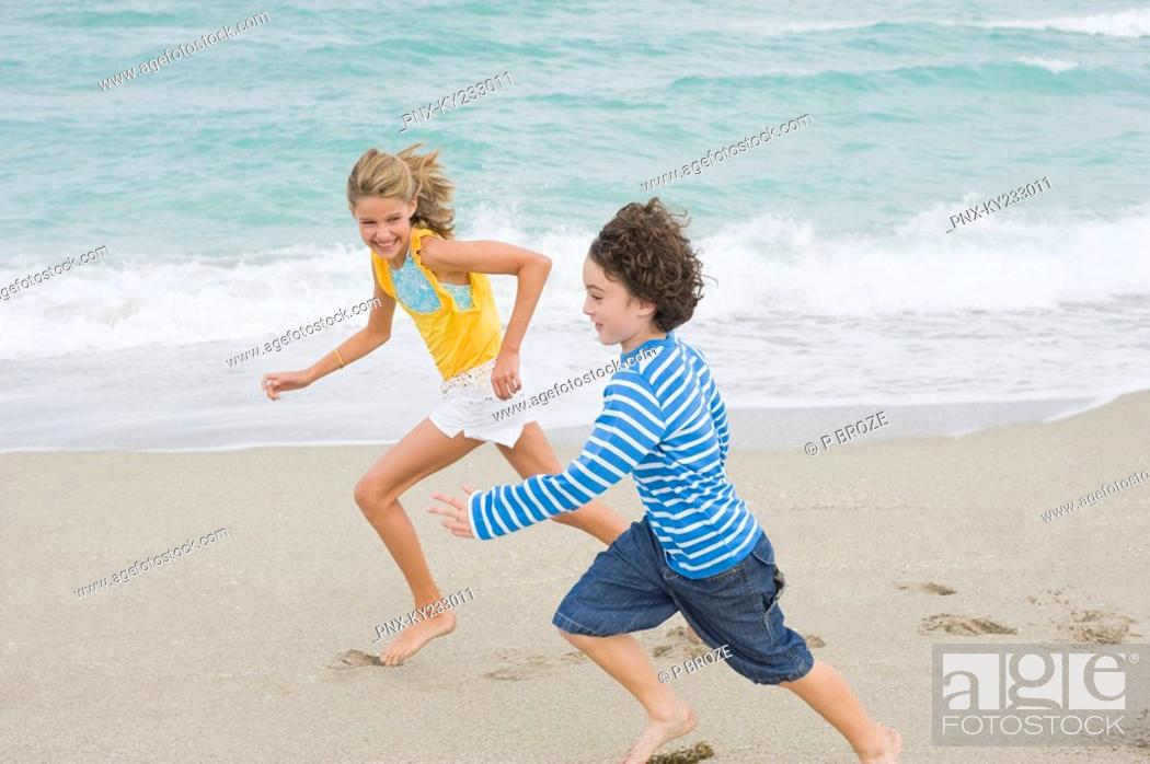 Stock Photo: Boy running with a girl on the beach.