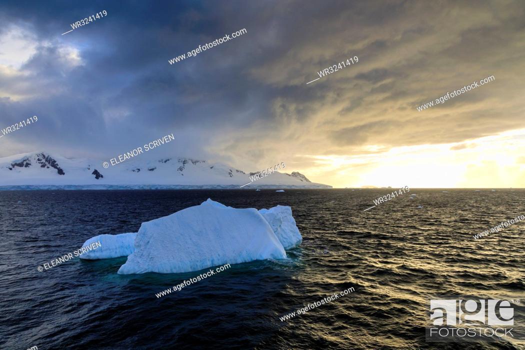 Imagen: Blue iceberg at sunset, with interesting cloud formations, Gerlache Strait, Antarctic Peninsula, Antarctica, Polar Regions.