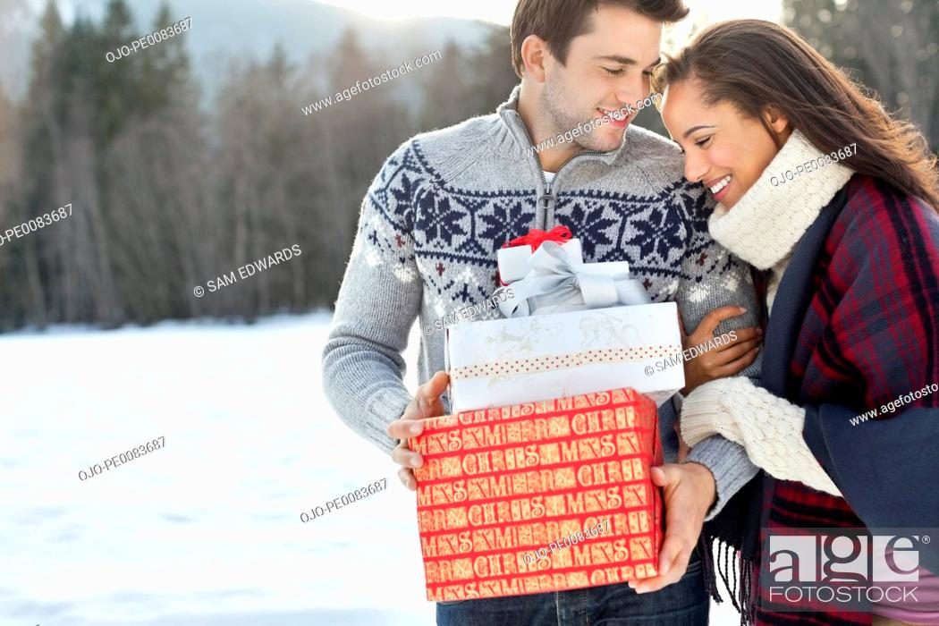 Stock Photo: Smiling couple hugging and holding Christmas gifts in snow.