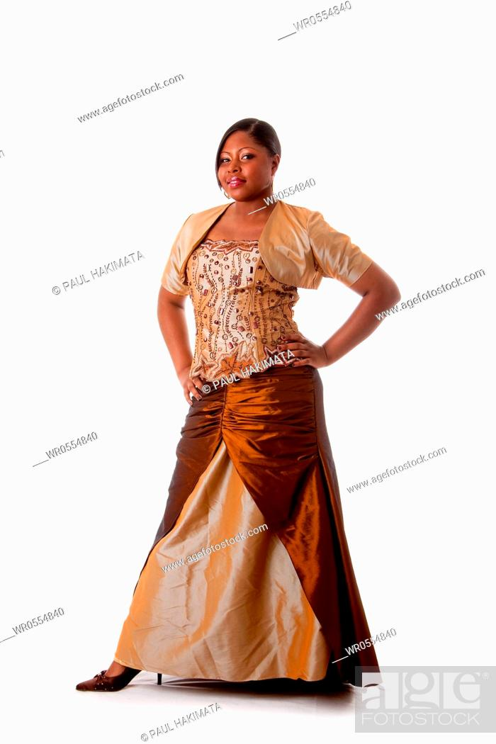 Imagen: Beautiful African American woman in brown with gold dress, hands on hips and standing, isolated.