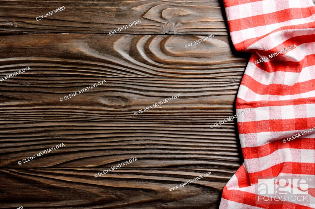 Stock Photo: Red checkered napkin on brown wooden kitchen table with copy-space. Top view.