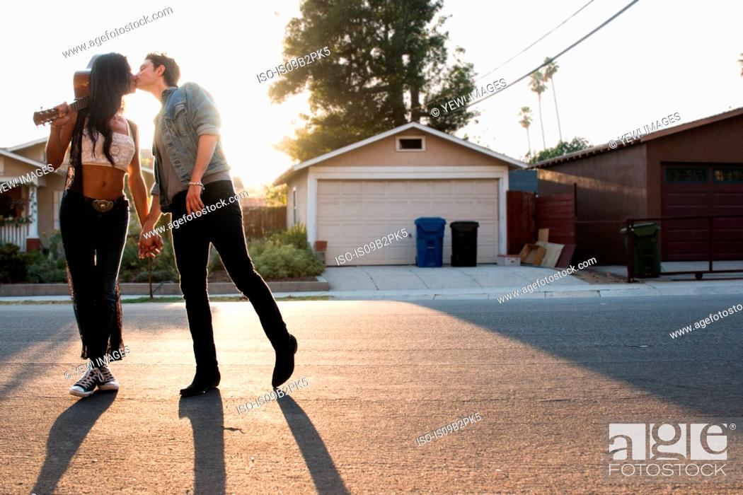 Stock Photo: Young couple outdoors, kissing, young woman holding guitar.