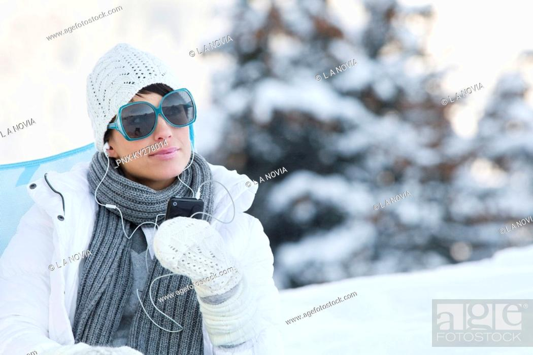 Stock Photo: Young woman listening to MP3 player in snow.