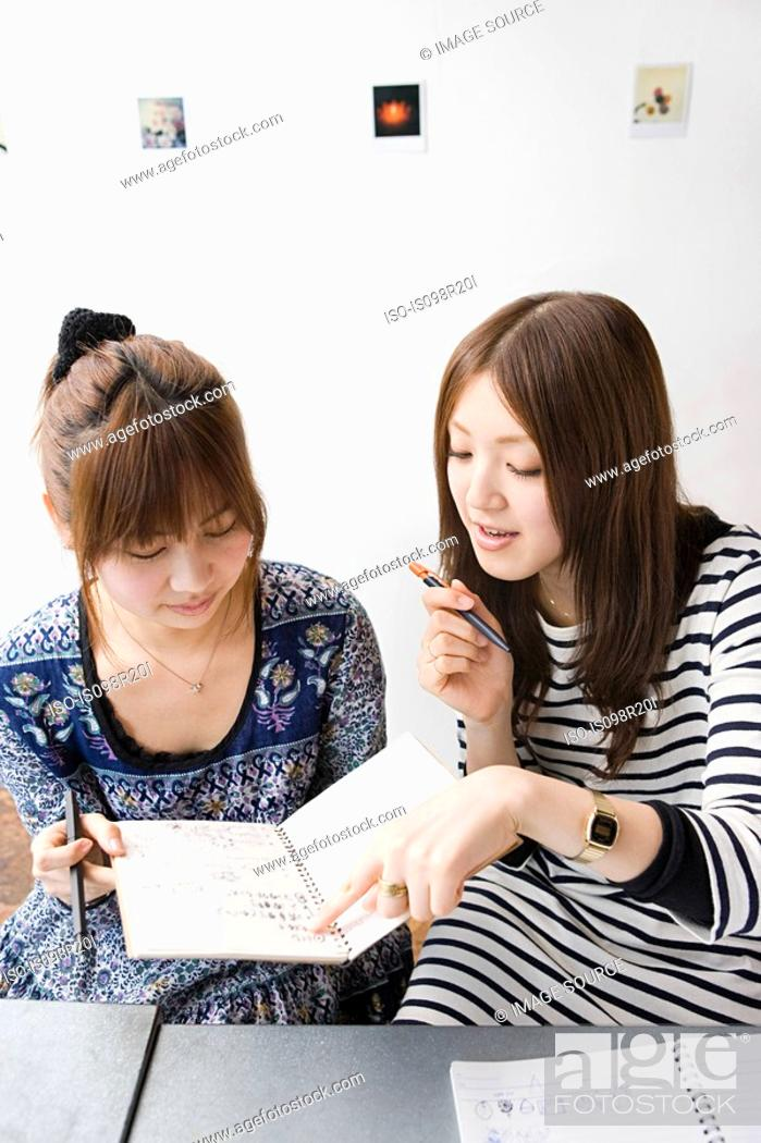 Stock Photo: Young women looking at note book.