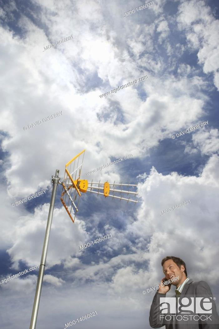 Stock Photo: Business man using cell phone underneath satellite tower.