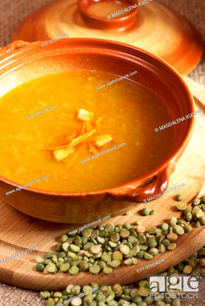 Photo de stock: Pea soup with carrot and bacon in pot.