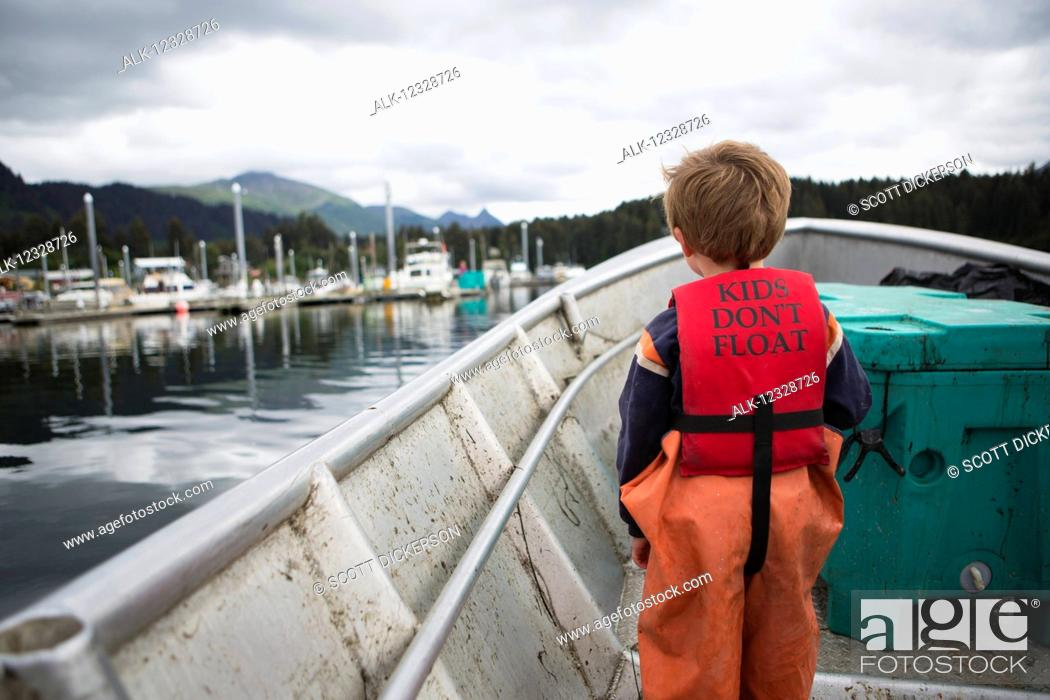 Imagen: Young boy stands in his family's set-net skiff with a life vest saying 'kids don't float', South-central Alaska; Seldovia, Alaska, United States of America.