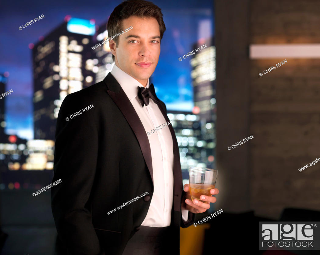 Stock Photo: Smiling man in tuxedo drinking cocktail.