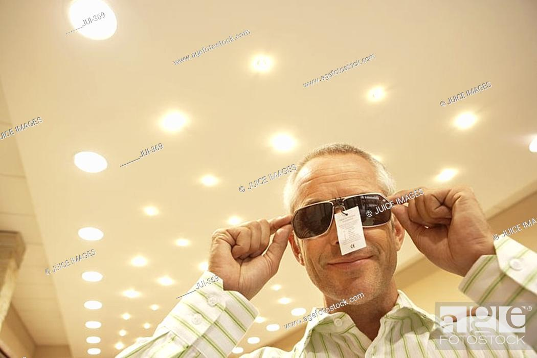 Stock Photo: Mature man trying on pair of sunglasses in shop, price tag attached, smiling, low angle view.