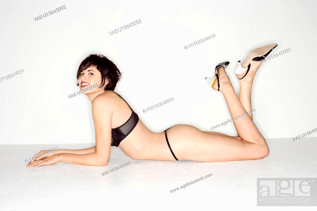Stock Photo: Young sexy Caucasian woman lying on floor wearing black lace underwear.