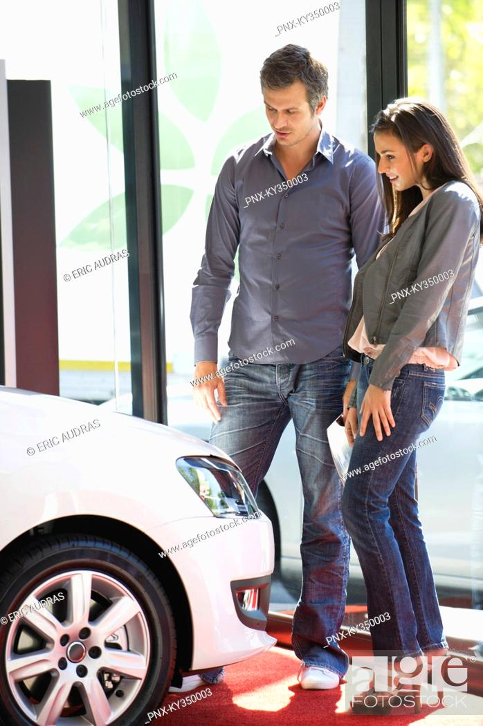 Stock Photo: Couple buying a car at showroom.