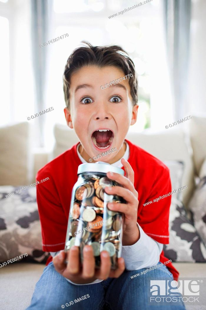 Stock Photo: Surprised boy holding jar full of coins.