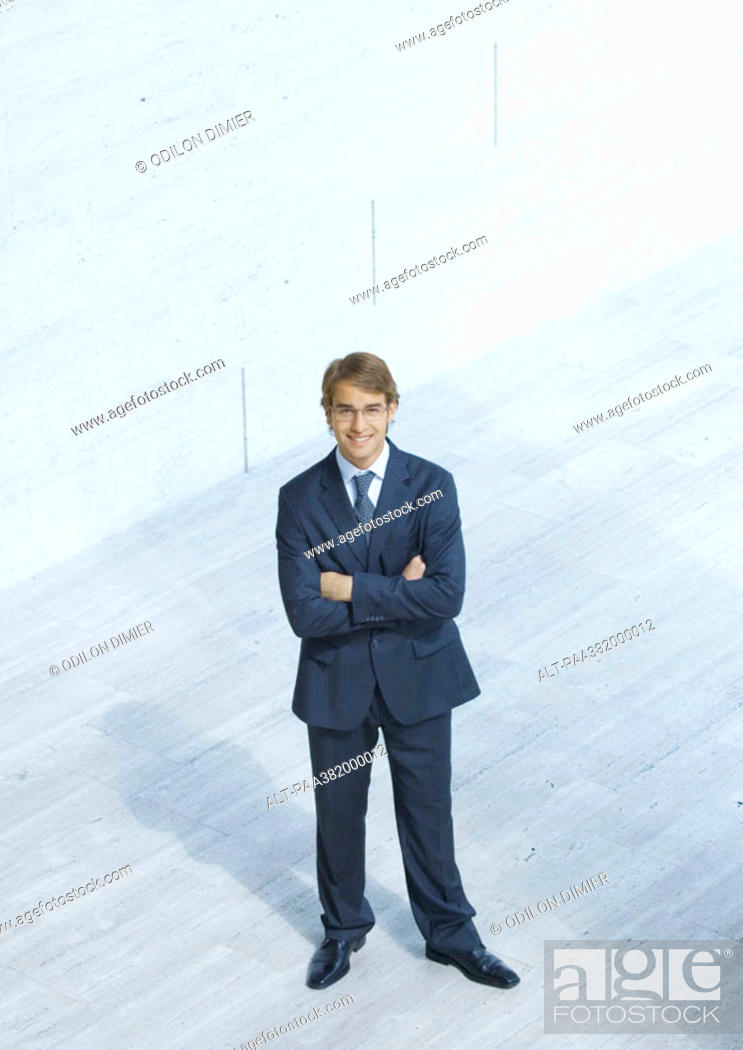 Stock Photo: Businessman standing with arms folded, high angle view.