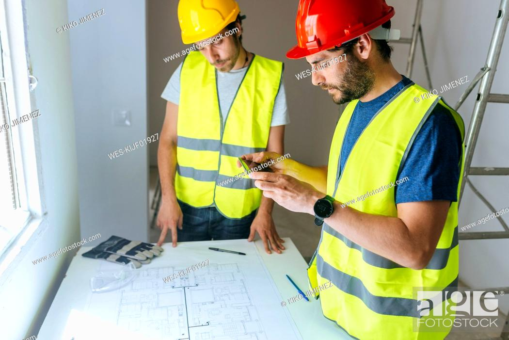 Stock Photo: Workers taking a picture of the plan with mobile phone.