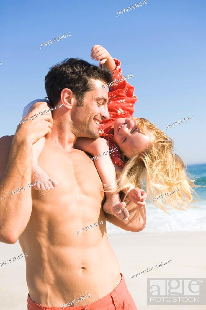 Stock Photo: Man carrying his daughter on his shoulders on the beach.