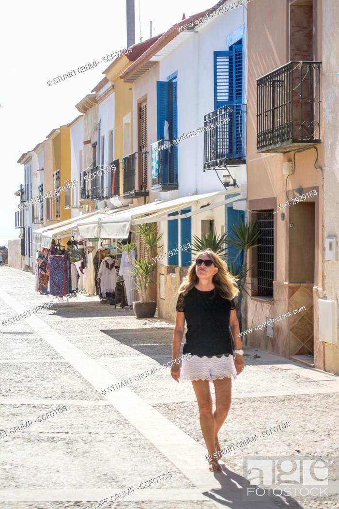 Photo de stock: Solo femail tourist walks down the main street of the Spanish island of Tabarca.
