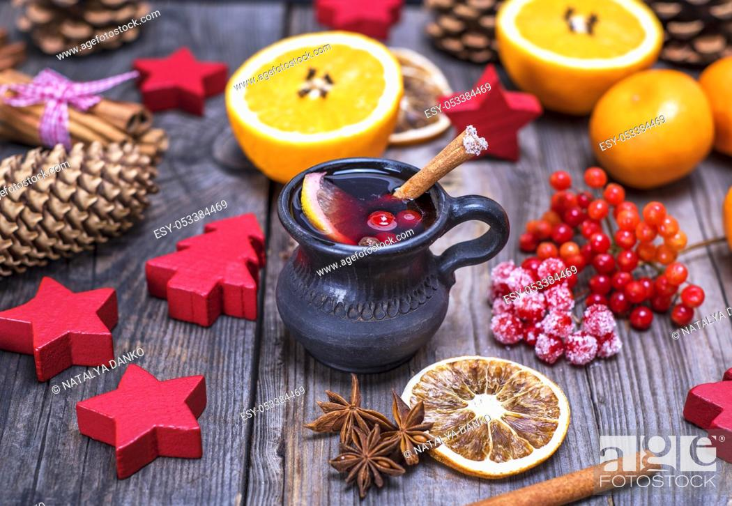 Stock Photo: mulled wine in a brown ceramic mug on a gray wooden background, beside ingredients and Christmas decor.