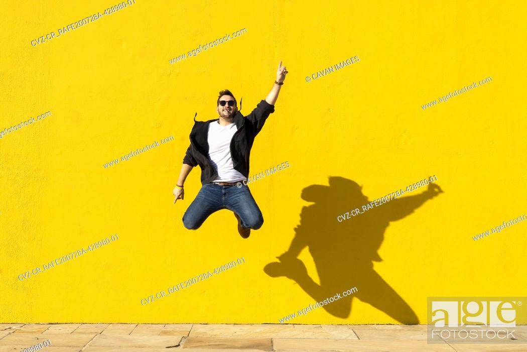 Stock Photo: Young man with sunglasses jumping in front of a yellow wall.