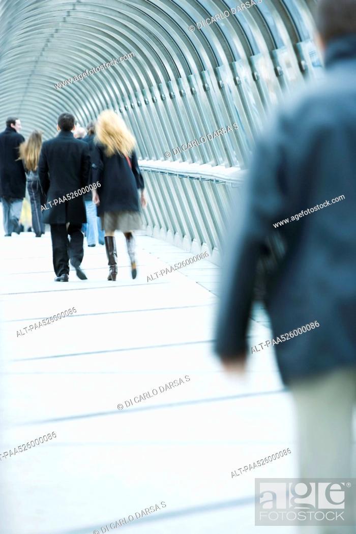 Stock Photo: Pedestrians walking across elevated walkway.