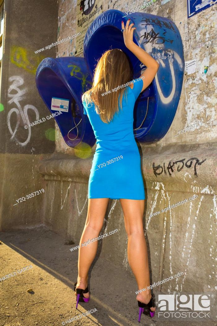 Stock Photo: Sexy and elegant Ukrainian woman wearing a blue dress posing reclining to a telephone booth for a photographic sequence in the ancient city of Lviv, Ukraine.