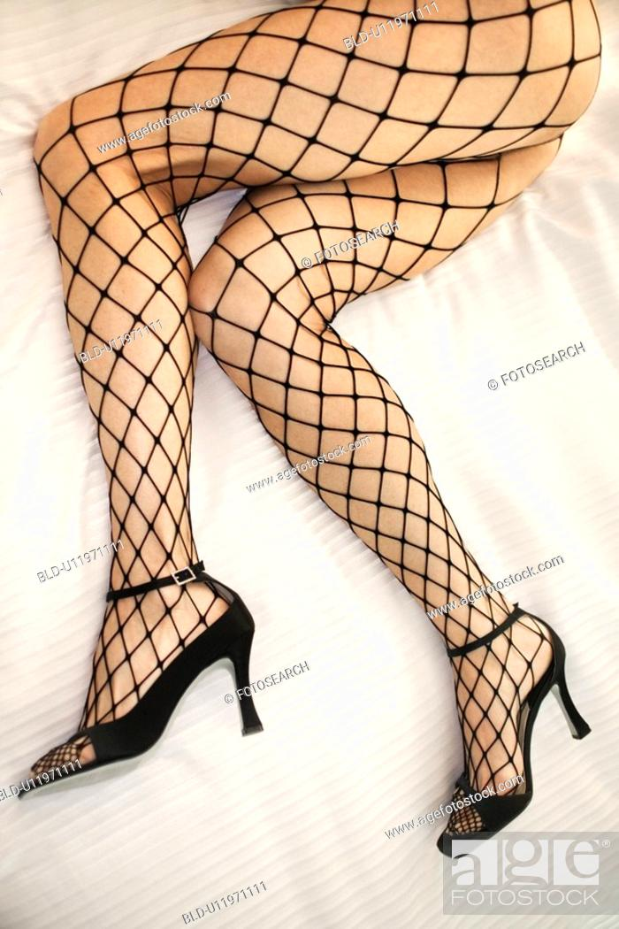 Stock Photo: Woman's legs laying on bed in fishnet stockings and high heel shoes.