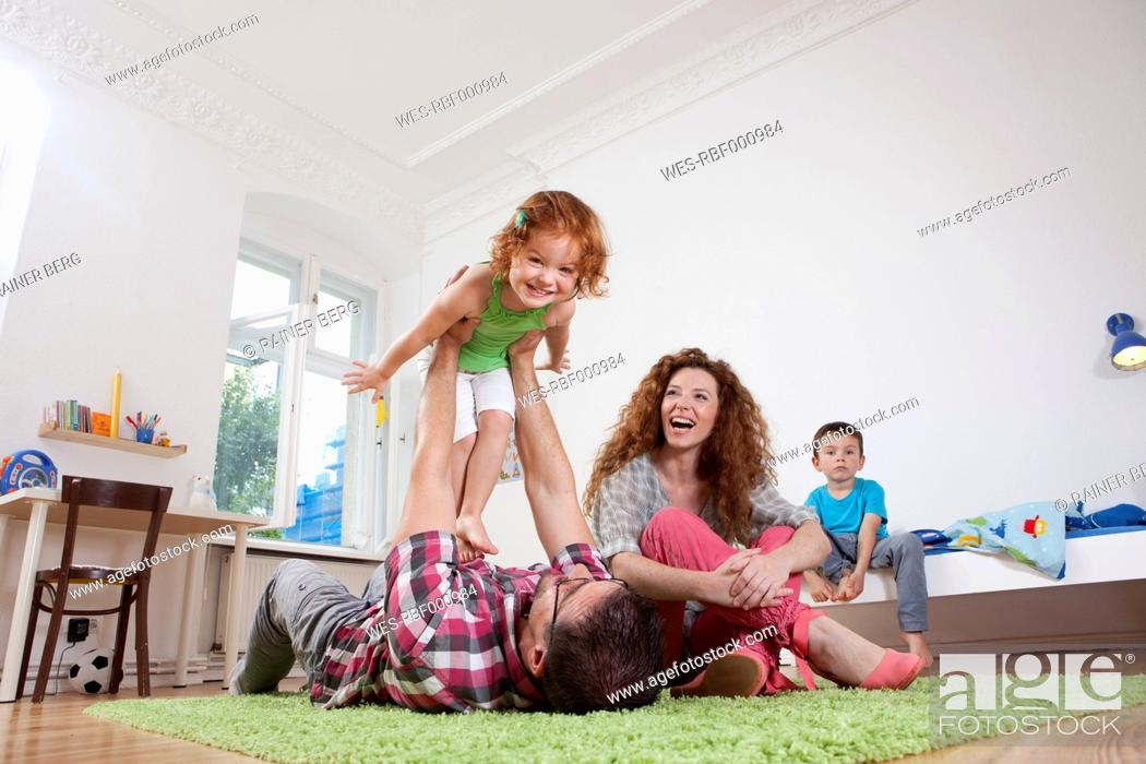 Stock Photo: Germany, Berlin, Father holding daughter, mother sitting besides, smiling.