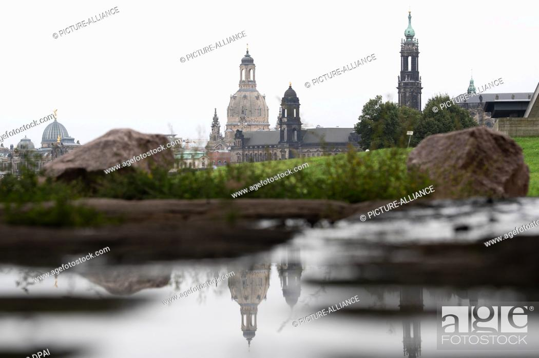 Stock Photo: 16 September 2021, Saxony, Dresden: The Frauenkirche (M) is reflected in a puddle next to the Katholische Hofkirche (r) on the banks of the Elbe.