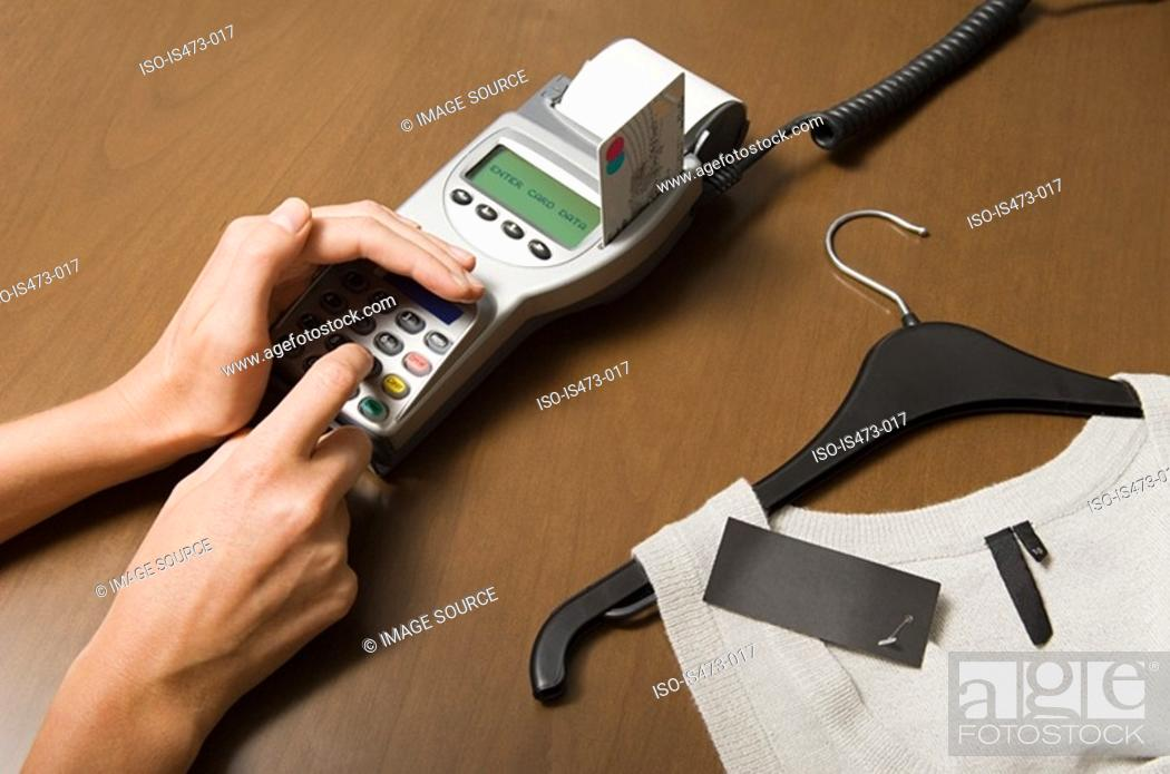 Stock Photo: Woman entering pin into credit card reader.
